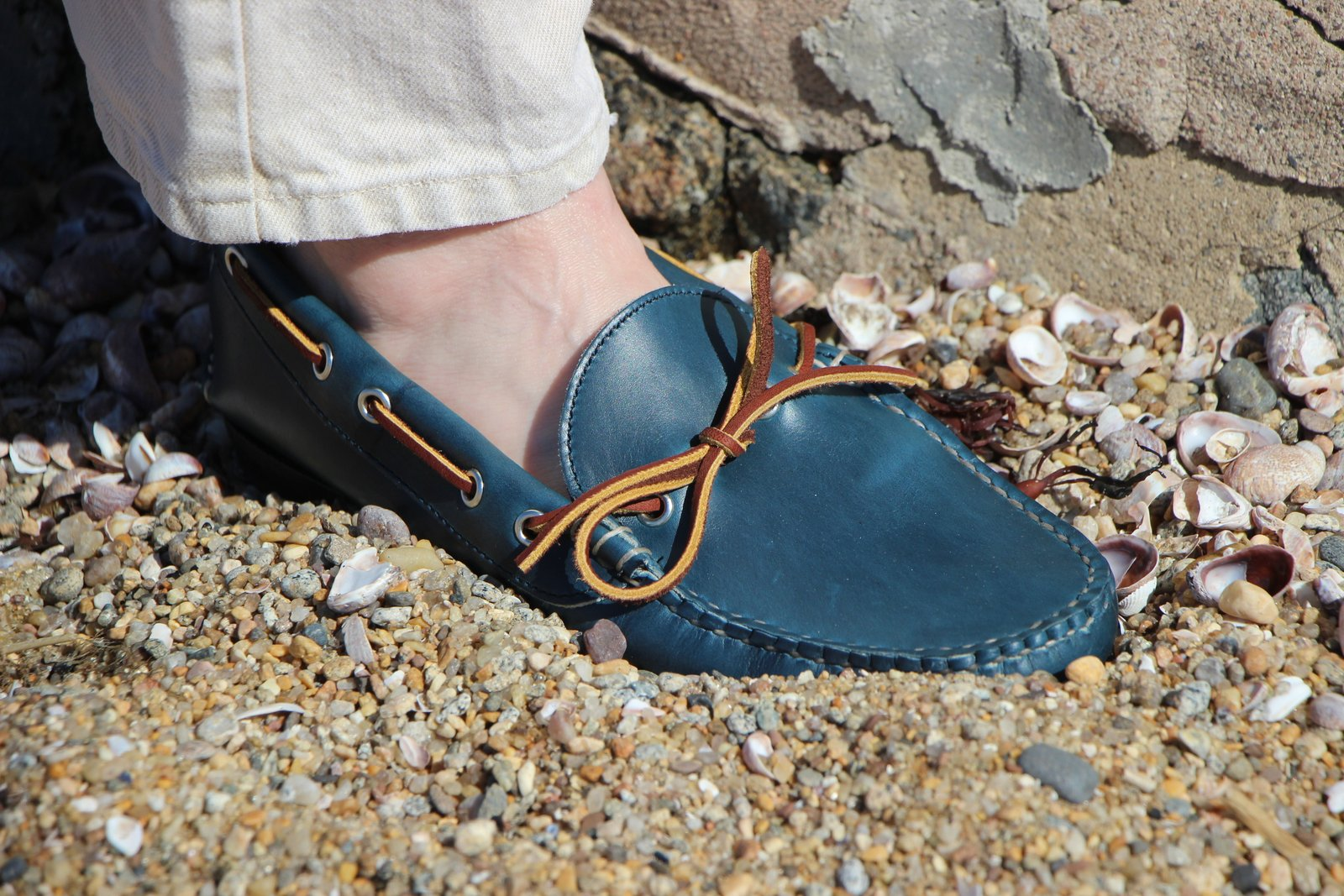 A blue and white shoes standing on a rock