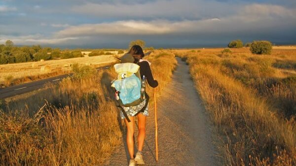 A girl wearing travel bag and walking on the road