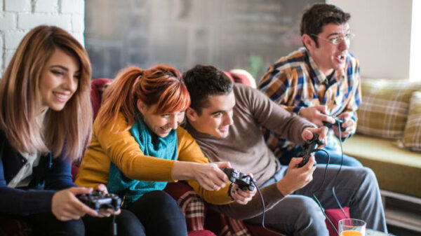 A group of people sitting on sofa and playing video game