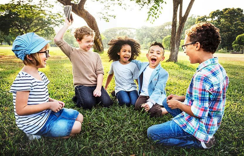 A group of kids sitting on a grass in park
